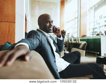 Happy Young Businessman Waiting At Hotel Lobby Making A Phone Ca