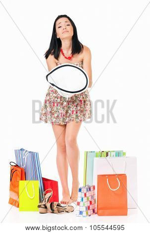 Shopaholic woman with many shopping bags holding hat, isolated on white background