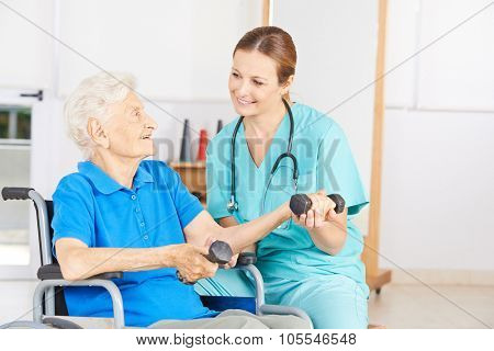 Smiling senior woman in wheelchair lifting dumbbells in physiotherapy