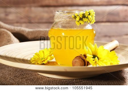 Honey, dipper and flowers on plate on sackcloth