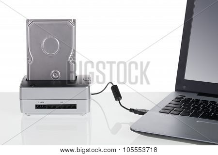 Hard Disk Drive With Docking Station Connected To A Laptop Computer. For Data Storage.