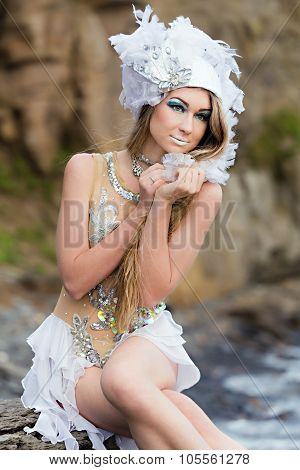 Girl Dressed Like A Mermaid Is Sitting On The  Beach