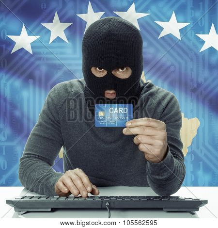 Dark-skinned Hacker With Flag On Background Holding Credit Card - Kosovo