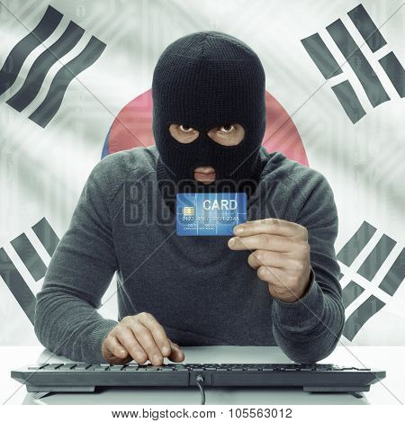 Dark-skinned Hacker With Flag On Background Holding Credit Card - South Korea