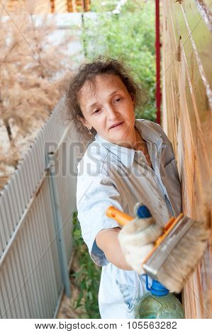 Pretty woman paints her wooden house