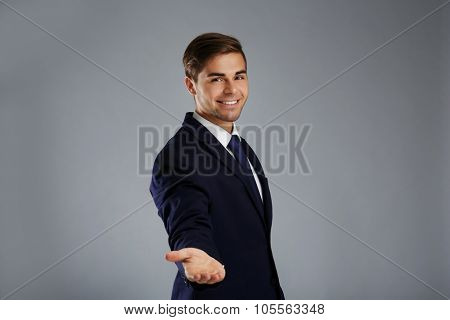 Elegant man in suit introduce something on gray background