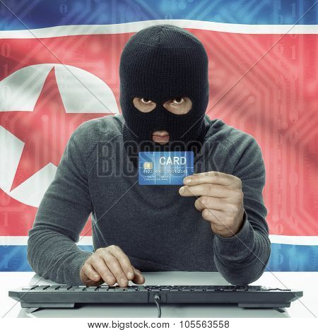 Dark-skinned Hacker With Flag On Background Holding Credit Card - North Korea