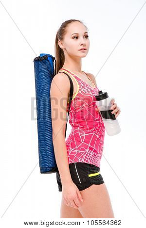Portrait of a beautiful sports woman with yoga mat and shaker standing isolated on a white background