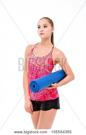 Young beautiful sportswoman in pink top and black shorts with blue yoga mat