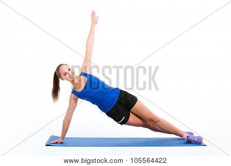 Full length portrait of a happy fitness woman doing yoga exercises on the mat isolated on a white background