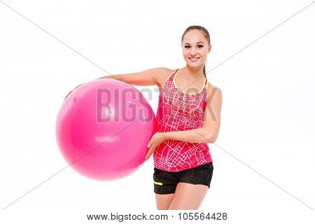 Young smiling beautiful sportswoman in pink top and black shorts holding fitball