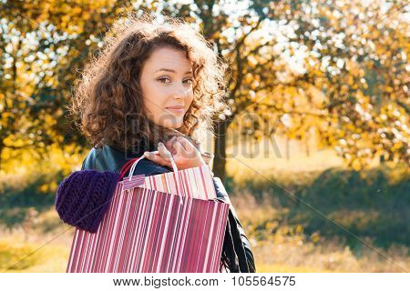 Portrait of a beautiful young woman with shopping bags and autumn background