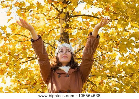 Young woman with outstretched arms and yellow leaves on a tree in a background