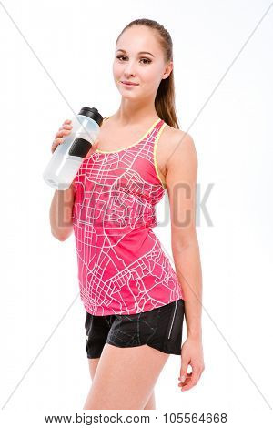 Portrait of a happy sports woman holding shaker and looking at camera isolated on a white background