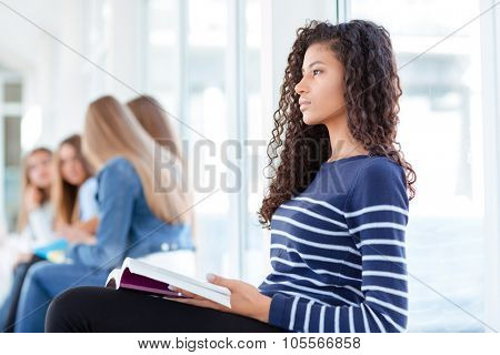 Portrait of a young afro american woman holding book and looking away in university hall