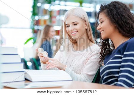 Blonde beautiful girl and african american curly young woman using cellphone