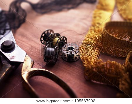 old sewing machine bobbins and fringe or lace tapes and silk trimmings with gold (brass) scissors on a old grungy work table. Intentionally shot in retro low key tone and shallow depth of field.