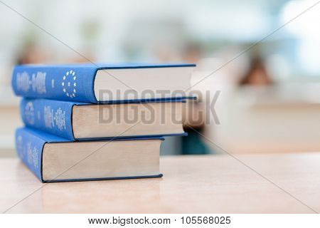 Three blue books are lying on the table