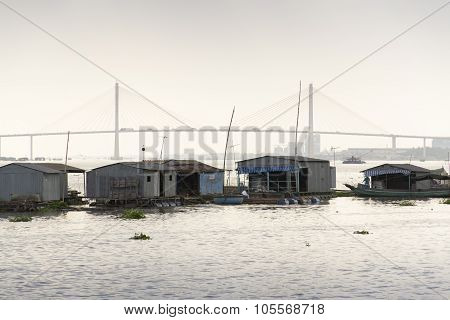 Ratty Boats And Raft Houses With Fish Cages Floating On Mekong River