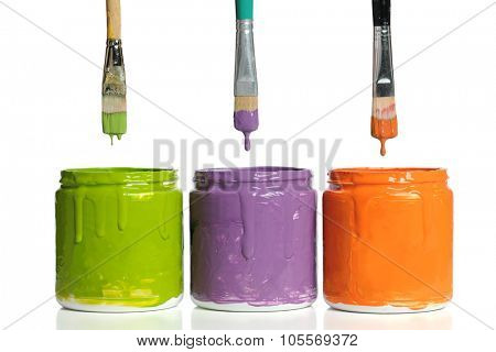 Paintbrushes dripping paint into containers with secondary colors isolated over white background