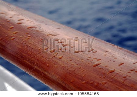 Wooden hand rail on an ocean liner with rain drops with the Caribbean ocean in the background.