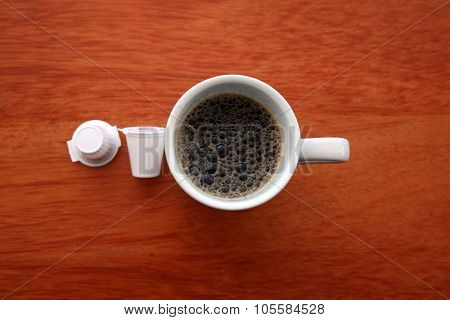 A classic Cup of Black Coffee with Cream Packets. Shot from top down for a unique view. White ceramic coffee mug with cream packets on a brown table.