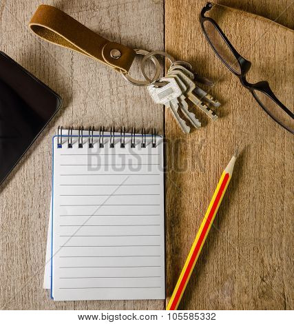 Blank Notepad, Key Chain, Eye Glasses And Mobile Phone On Wooden Table