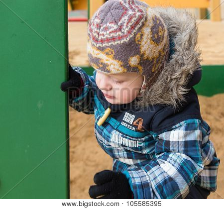 The Kid Gets On A Sandbox Side At A Playground And Looks For A Corner
