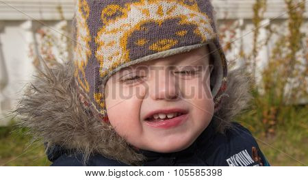 Face Of The Little Boy In A Warm Cap With The Covered Eyes And A Contemptuous Grimace