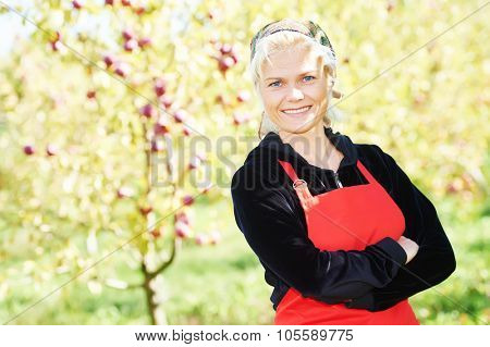 Young woman picker portrait during ripe apples picking from an tree on summer day in orchard