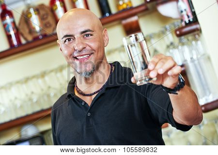 Portrait of sommelier barman holding a glass of water with wine glasses in the bar background