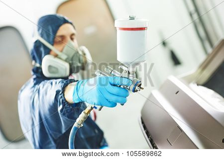 Close-up of spray gun using by mechanic worker during painting auto car bumper in a paint chamber