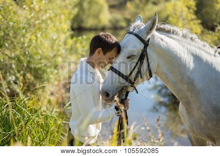 Man stands near the lake with a horse