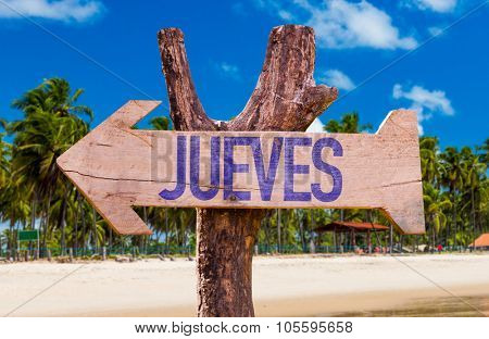 Thursday (in Spanish) arrow with beach background