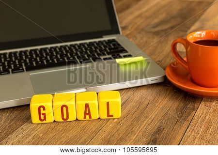 Goal written on a wooden cube in front of a laptop