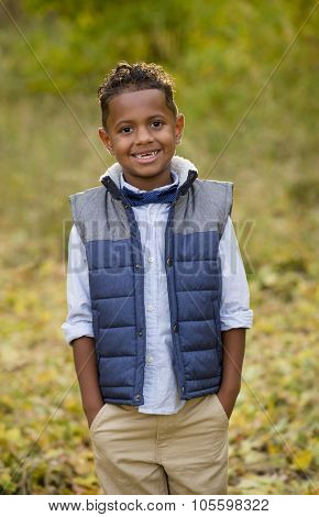 Cute outdoor portrait of a smiling African American young boy