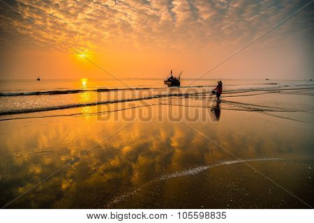 People work on a beach in sunrise