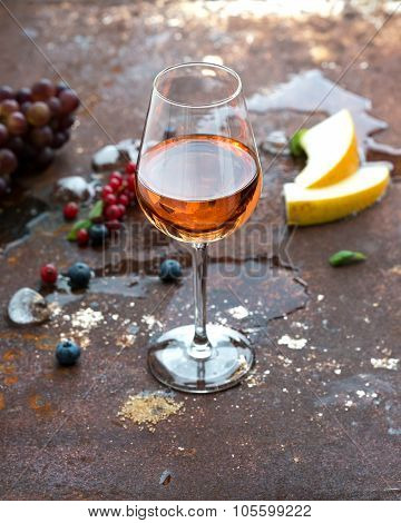 Glass of rose wine with berries, melon, grapes and ice on grunge rusty metal background