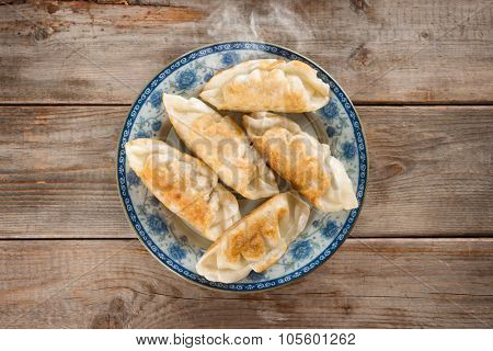 Top view fresh pan fried dumpling on plate. Chinese dish with hot steams on rustic vintage wooden background. Fractal on the plate is generic print.