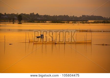 Fisher on boat in water season in sunrise in Dong Thap, Vietnam