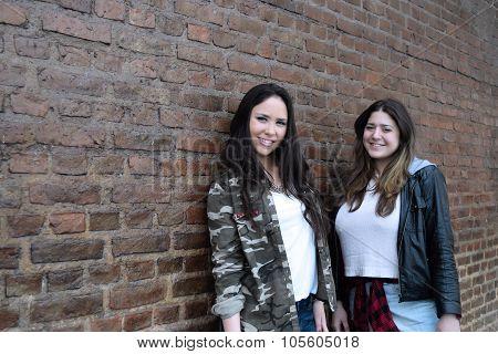 Two Hispanic Women Against A Brick Wall.
