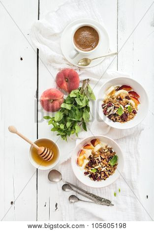 Healthy breakfast. Bowl of oat granola with yogurt, fresh fruit, mint and honey. Coffee, vintage sil