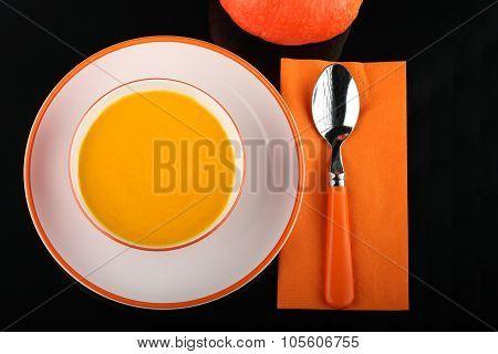 Bowl Of Pumpkin Hokkaido Soup On White Plate On Black Sheet