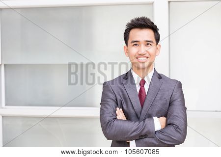 Asian Businessman Standing Arms Crossed And Smiling