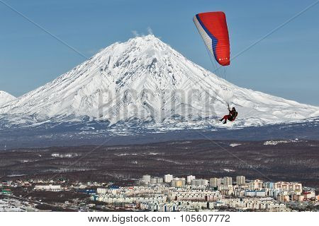 Paraglider Flying Over Town On Background Of Active Volcano
