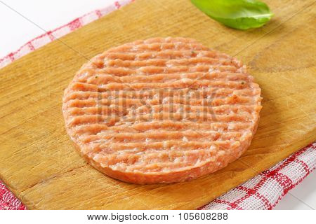 close up of raw burger patty on wooden cutting board