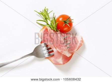 slice of smoked pork neck with rosemary and cherry tomato impaled on fork