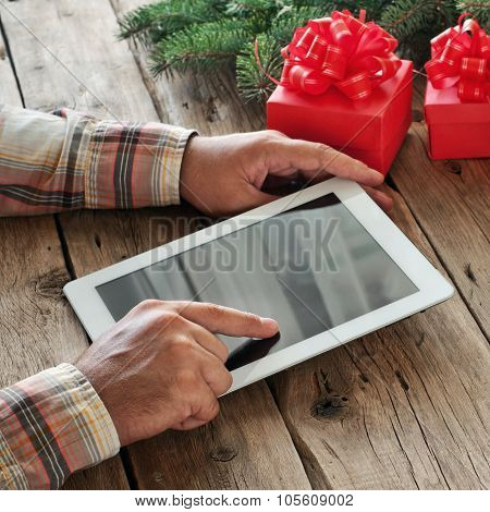 Tablet Computer In Men Hands. Near The Table With Tablet Computer Three Gift Boxes, Christmas Toys,
