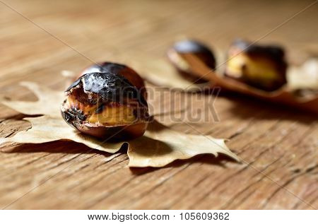 some roasted chestnuts, typical snack in All Saints Day in Catalonia, Spain, on some dry leaves on a rustic wooden surface