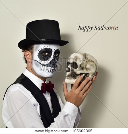 a man with mexican calaveras makeup, wearing bow tie and top hat, with a skull in his hand, and the text happy halloween